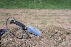 在堆的园艺工具土和草 免版税库存图片