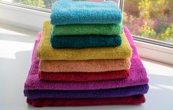 在堆的多彩多姿的双重毛巾在窗口 免版税库存照片