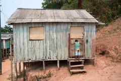 在堆的小屋和男孩在泥背景的村庄 库存照片