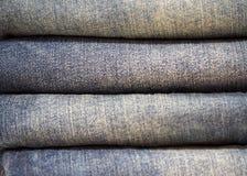 在堆的牛仔裤长裤在架子,特写镜头 图库摄影