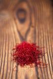 在堆的番红花香料在老织地不很细木背景 免版税库存图片
