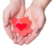 在堆的红色心脏在男性棕榈的纸心脏上 免版税库存图片