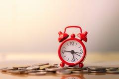 在堆的红色闹钟在储款和金钱生长或者能量救球的概念的硬币 图库摄影