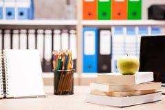在堆的绿色苹果在一个笔记本和铅笔旁边的书在t 免版税图库摄影
