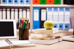 在堆的绿色苹果在一个笔记本和铅笔旁边的书在t 免版税库存图片