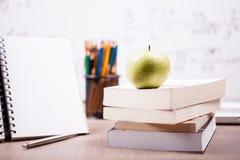 在堆的绿色苹果在一个笔记本和铅笔旁边的书在t 免版税库存照片