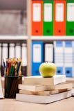 在堆的绿色苹果在一个笔记本和铅笔旁边的书在t 库存照片