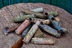 在堆的老色的弹药筒在一个木树桩 免版税库存图片