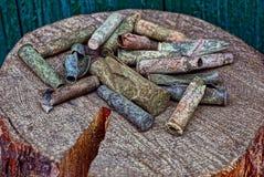 在堆的老色的弹药筒在一个木树桩 免版税图库摄影