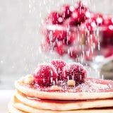 在堆的薄煎饼自创蛋糕装饰用莓果结冰的樱桃洒与在白色板材的糖粉末 库存照片