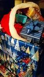 在堆的被包裹的礼物与圣诞老人帽子 库存图片