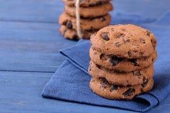 在堆的被堆积的巧克力饼干在蓝色木桌上的美丽的餐巾 bacterias 美味 库存图片