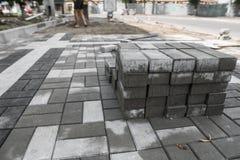 在堆的路面鹅卵石在街道上 边路的混凝土或花岗岩灰色方形的路面平板 免版税库存照片