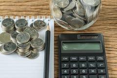 在堆的选择聚焦与铅笔和笔记本,作为财政挽救概念的计算器的硬币 图库摄影