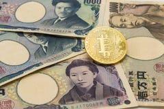 在堆的金黄Bitcoin许多键入日本钞票背景 免版税库存照片