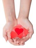 在堆的玻璃心脏在女性棕榈的心脏上 免版税库存照片