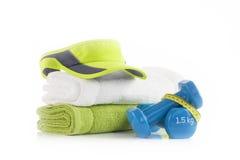 在堆的绿色网球头饰带盖帽与两涂哑铃被包裹的蓝色乙烯基的白色和绿色毛巾用黄色测量的t 免版税库存图片