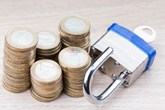 在堆硬币旁边打开挂锁 免版税库存照片