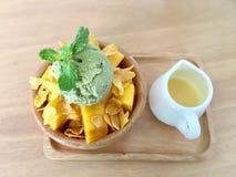 在堆Su的甜黄色芒果与绿茶冰淇凌和甜奶油在白色瓶子在木背景 免版税库存图片