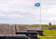 在堡垒乔治,苏格兰旗子的大炮在背景中 免版税库存照片