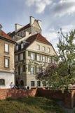 在堡垒墙壁附近的五颜六色的房子在老镇在华沙 樱桃绽放 库存图片