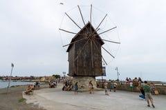 在堤防的一台老木风车在老镇 免版税库存照片