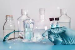 在塑料小瓶的两个液体样品在手套的手上 库存图片