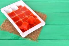 在塑料形状的冷冻西红柿汁在木背景 生活乱砍,单一方式存放菜 免版税库存照片
