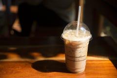 在塑料杯子的冷的咖啡在咖啡馆的棕色木桌上 免版税库存照片