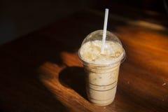 在塑料杯子的冷的咖啡在咖啡馆的棕色木桌上 免版税库存图片