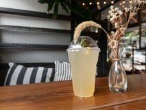 在塑料杯子的柠檬水在木桌上 库存照片