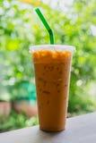 在塑料杯子的泰国被冰的牛奶茶在木桌上 免版税图库摄影