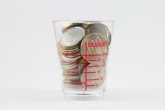在塑料杯子的硬币 免版税库存照片
