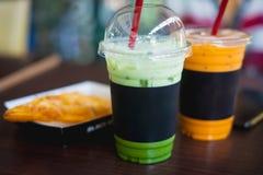 在塑料杯子的绿色泡影茶在木桌上 美好的p 免版税库存图片