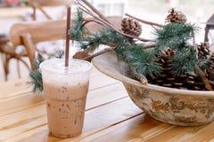 在塑料杯子的被冰的咖啡在与杉木锥体的桌上 免版税图库摄影