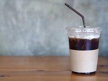 在塑料杯子的被冰的无奶咖啡在木桌上 免版税图库摄影