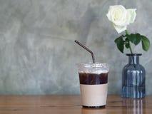 在塑料杯子的被冰的无奶咖啡在木桌,白色玫瑰bac上 库存图片