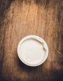 在塑料杯子的酸奶在土气木背景 库存照片