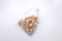 在塑料清楚的袋子的大蒜在白色背景 图库摄影