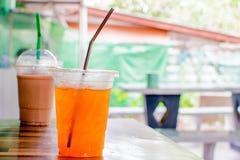 在塑料玻璃的被冰的茶有被弄脏的背景 免版税库存照片