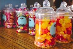 在塑料瓶子的五颜六色的糖果在架子 免版税库存照片