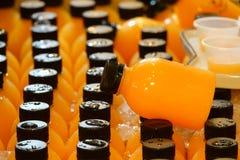 在塑料瓶的橙汁过去在冰待售 免版税图库摄影