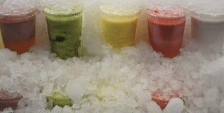 在塑料的果汁拿走玻璃在冰块下 图库摄影