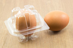 在塑料盒的两个未加工的鸡蛋在木委员会 库存图片