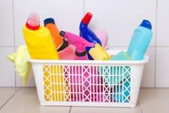 在塑料盒的清洁物品在铺磁砖的地板上 免版税库存图片