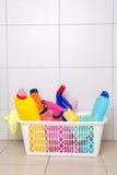 在塑料篮子的清洁物品在铺磁砖的地板上 免版税库存图片