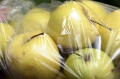 在塑料胶膜包装的黄色金黄苹果 免版税库存图片