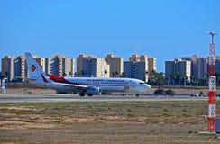 在塔式大楼前面的阿尔及利亚航空公司飞机在阿利坎特机场 库存照片