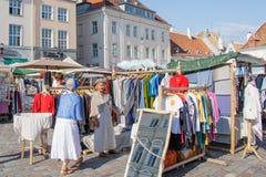 在塔林城镇厅正方形的市场  选择礼服的一个老妇人 免版税图库摄影