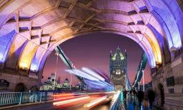 在塔桥梁上在日落以后的伦敦与通过被弄脏的红色的公共汽车  免版税库存图片
